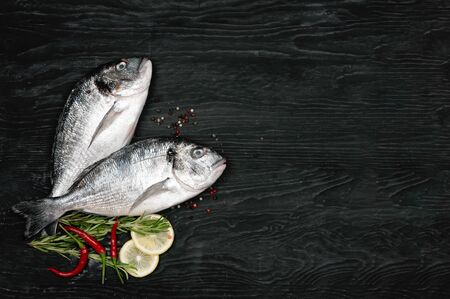 Fresh fish dorado. Dorado and ingredients for cooking on a black table. 写真素材 - 129449995