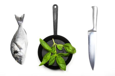 Fresh fish dorado, knife and frying pan with basil leaves on a white background. View from above. 写真素材