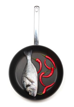 Fresh fish dorado with chilli on a frying pan on a white background. View from above. 写真素材 - 129450161