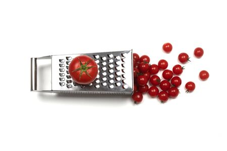 Tomatoe on a grater and cherry tomatoes. One to many separation concept. 写真素材 - 129450188