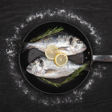 Fresh fish dorado. Dorado and ingredients on a frying pan for cooking on a table. 写真素材