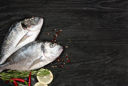 Fresh fish dorado. Dorado and ingredients for cooking on a black table.