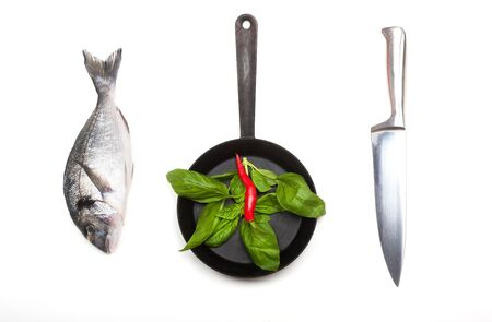 Fresh fish dorado, knife and frying pan with basil leaves and red chilli on a white background. View from above. 写真素材