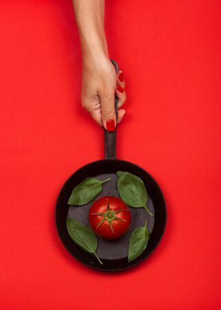 Fresh tomato on frying pan with basilic. Isolated on red background. 写真素材