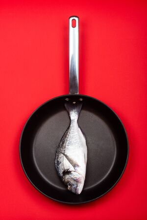 Fresh fish dorado on a frying pan on a red background. View from above.