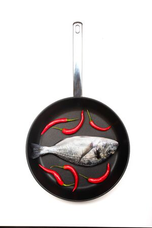 Fresh fish dorado with chilli on a frying pan on a white background. View from above. 写真素材