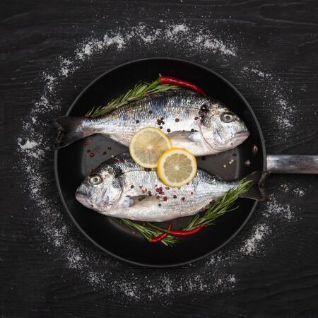 Fresh fish dorado. Dorado and ingredients on a frying pan for cooking on a table. 写真素材 - 129450823