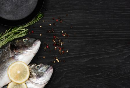 Fresh fish dorado. Dorado and ingredients for cooking on a black table. 写真素材 - 129450816