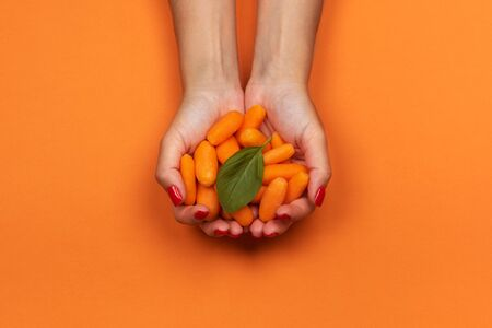 Baby carrot in girls hands. Isolated on orange background. 写真素材 - 129450831