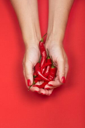 Female hands holding a handful of fresh red hot chilli peppers. Isolated on red background. 写真素材 - 129450837