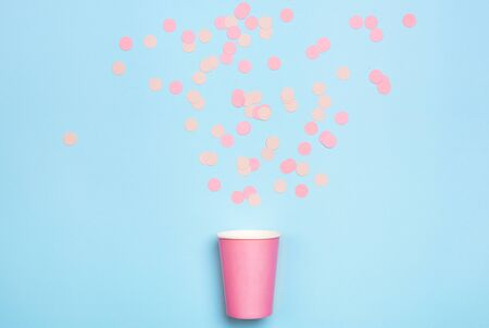 Drinking paper cup with confetti scattered on a mint blue background. Flat lay composition. Birthday celebration. Greeting card poster template.