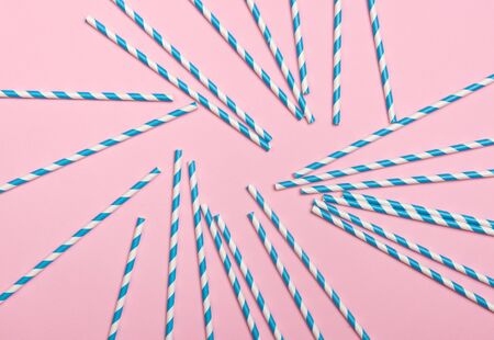 Striped coctail straws on pink background. Birthday party celebration abstract fashion baby shower concept. Minimalist pastel flatlay style.