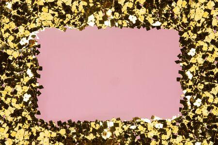 Golden confetti glitter frame on pink background. Festive holiday pastel backdrop. Greeteng cards template. Archivio Fotografico - 132126361