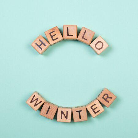 Hello winter word written on wood block. Greeteng card concept on mint background. Stock Photo