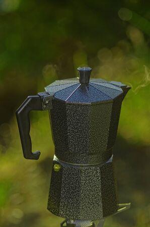 An espresso coffee pot on a single burner camp stove Stock Photo