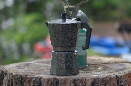 An espresso coffee pot and single burner camp stove on a log