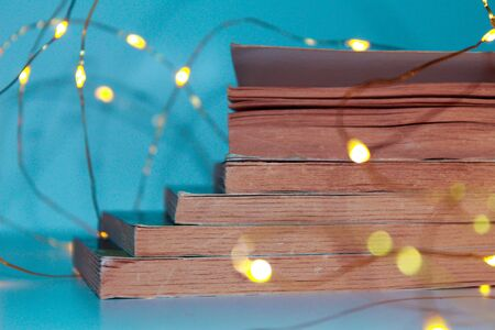 image of a stack of vintage style books with warm lights and turquoise blue background