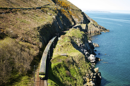The Cliff Walk is a linear walk between Bray and Greystones, following the train line along the cliffs of Bray Head. This well maintained walk offer stunning and dramatic views along steep cliffs into the Irish Sea.  Take one of the many trains to get bac Stock Photo