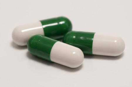 enfermedades mentales: Tres c�psulas o pastillas en el fondo blanco