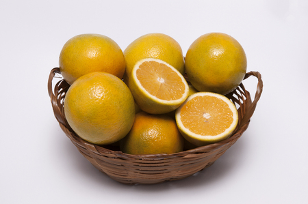 A Wicker Basket With Oranges on white background / Fruits