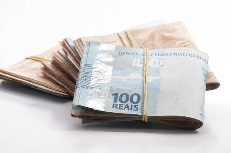 bankroll: A few bills of brazilian currency (real) on white background
