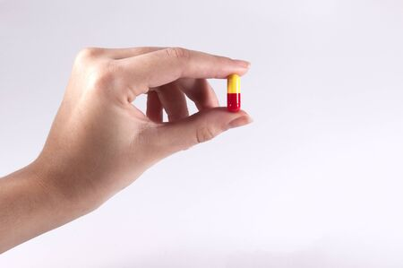 Caucasian Woman Holding a Pill on White Background / Capsules and Pills / Medicine Stock Photo
