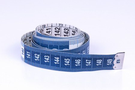 A tape measure or measuring tape is a flexible ruler on white background Stock Photo
