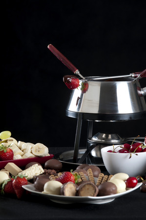 Fondue melted chocolate dip with different flavors on black background