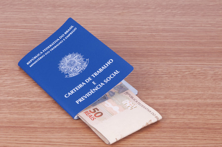 paycheck: Brazilian work document and social security document (carteira de trabalho) and brazilian currency (Real) Stock Photo