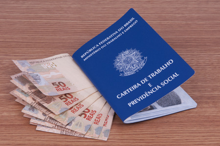 Brazilian work document and social security document (carteira de trabalho) and brazilian currency (Real) Editorial