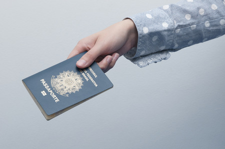 Caucasian Woman holding a brazilian passport / A passport is a government-issued document that certifies the identity and nationality of its holder for the purpose of international travel.