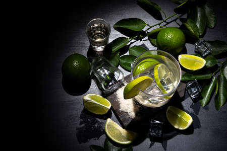 Caipirinha typical Brazilian drink with cachaca, lemon and sugar on dark background. Top view.