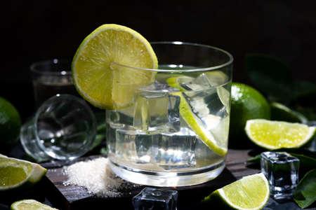 Caipirinha typical Brazilian drink with cachaca, lemon and sugar on dark background.