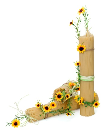 Uncooked Italian spaghetti decorated with yellow flowers isolated on white background photo