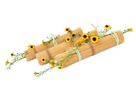Uncooked Italian spaghetti decorated with yellow flowers isolate on white background photo