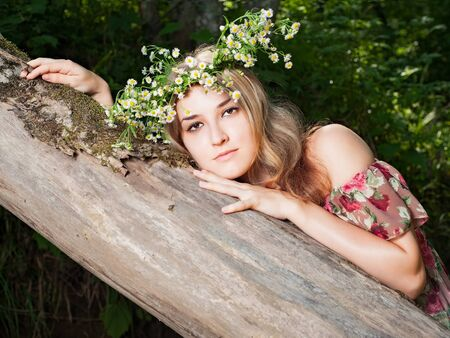 Beautiful girl in the national dress and and a wreath stand in the  forest