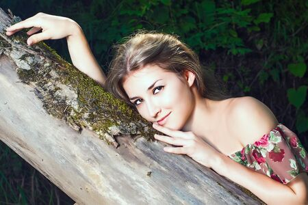 Beautiful girl in the national dress stand in the  forest