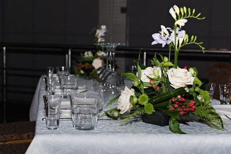 Flower composition of freesia, roses and hypericum on tables set for dining  Stock Photo
