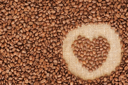 heart coffee frame made of coffee beans on burlap texture   photo