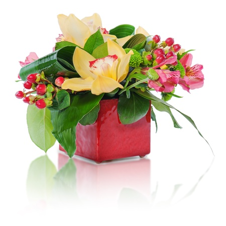 colorful floral bouquet of roses, cloves and orchids arrangement centerpiece in vase isolated on white background photo