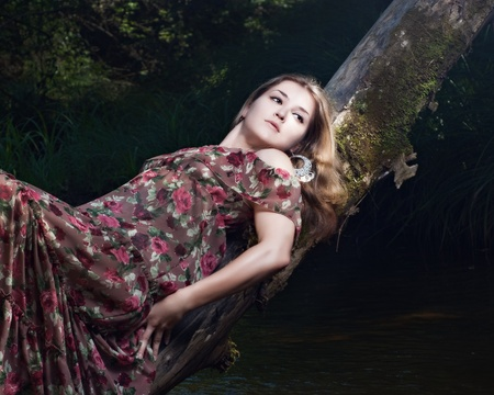 Beautiful girl in the national dress in the forest