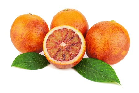 Ripe red blood oranges with cut and green leaves isolated on white background  Closeup  photo