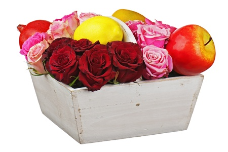 Flower arrangement of red roses and fruits in wooden basket isolated on white background. Closeup. Stock Photo - 20841315