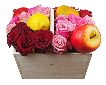 Flower arrangement of red roses and fruits in wooden basket isolated on white background. Closeup. Stock Photo - 20841316