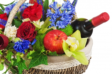 Flower arrangement of roses, orchids, fruits and bottle of wine in basket isolated on white background. Closeup.