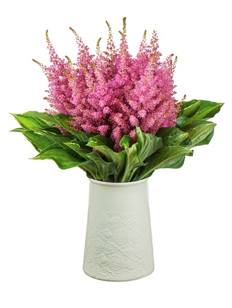 Colorful bouquet from astilbe and funkia flowers in vase isolated on white background. Closeup. photo
