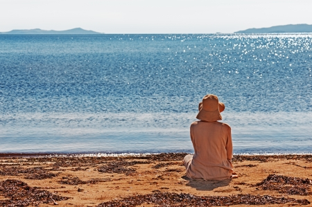Portrait of young woman on the beach near the sea sitting wearing dress and hat. Photo from behind. photo
