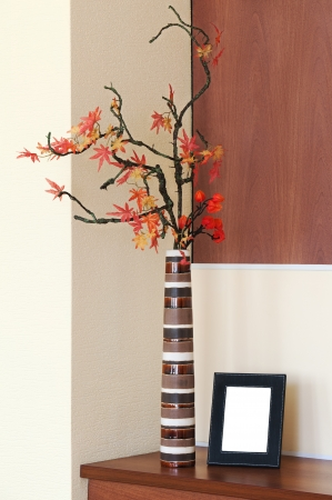 autumn arrangement: Autumn arrangement in a vase on the table and photoframe with place for your foto. Stock Photo