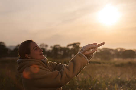 Outdoor fashion closeup portrait of pretty young woman with raised hands. Woman posing in autumn sunny sunset. photo