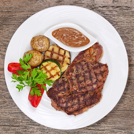 dinner plate: Grilled steaks, baked potatoes and vegetables on white plate on wooden background.